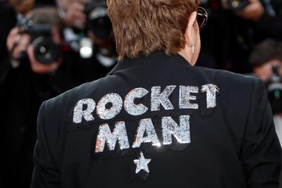 El cantante vestía una chaqueta negra que llevaba en la espalda bordado en lentejuelas plateadas el título de su canción Rocket Man, que da nombre también a la película, y un cohete igualmente de lentejuelas en la solapa.