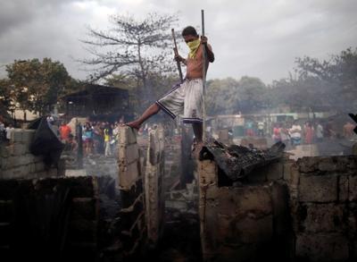 Un joven observa los restos de unas chabolas calcinadas tras un incendio de una zona deprimida en Paranaque.