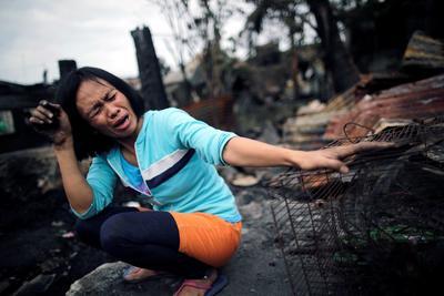Una mujer llora junto a los restos calcinados de su hogar.