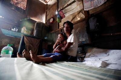Elena Valeña y su hija descansan en el interior de su casa en una zona deprimida de Quezon.