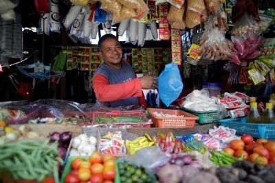 Federico Indicio, de 50 años, despacha a un cliente en su puesto en un mercado.