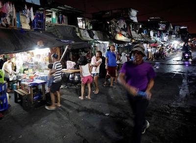 Varias personas caminan por un mercado en una zona deprimida de Manila.