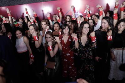 Más de 50 mujeres profesionales del mundo del cine muestran brazaletes rojos amarrados a sus muñecas como parte de la iniciativa #YaEsHora en defensa de la igualdad de género, en la alfombra de la 61 edición de los Premios Ariel.