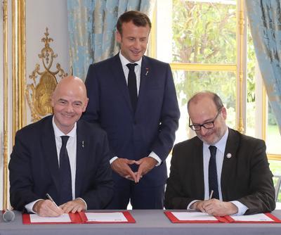El presidente francés, Emmanuel Macron, sonríe este lunes durante la firma de un acuerdo entre el presidente de la FIFA, Gianni Infantino, y el director de la Agencia Francesa de Cooperación, Remy Rioux.