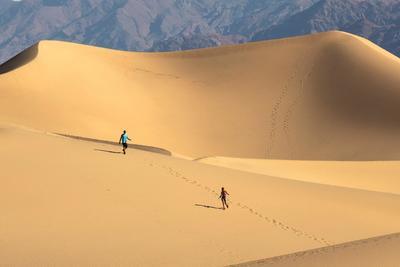 Dos turistas caminan por las dunas de Mesquite, en el Valle de la Muerte.