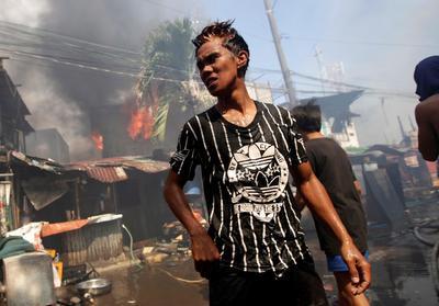 Varias personas intentan extinguir las llamas de un incendio declarado en un barrio de chabolas.