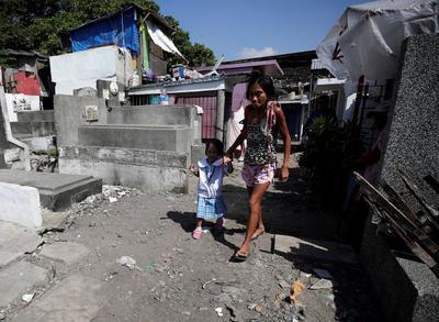 Michaela Sipalay lleva a su hija a la escuela entre las tumbas de un cementerio donde se encuentra su casa.