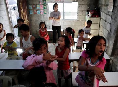 Niños juegan en la clase de una guardería en una zona deprimida de Quezon.