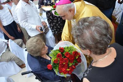 El obispo bajó hasta donde estaba para entregarle un ramo de flores.