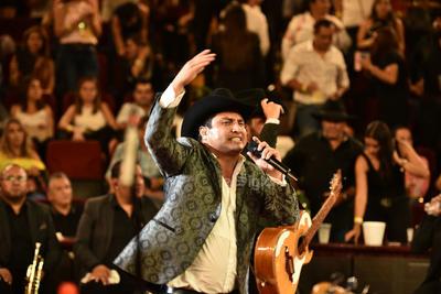 En su concierto, lució un pantalón y sombrero negro con un saco gris con decorados,