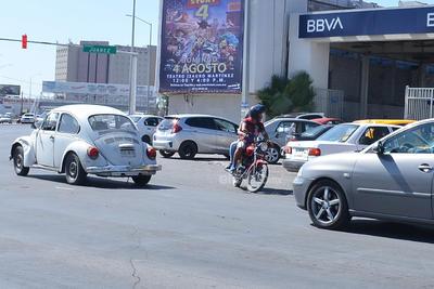 En sentido contrario. Ciudadano manejando en sentido contrario sobre carril donde automovilistas dan vuelta a la derecha.