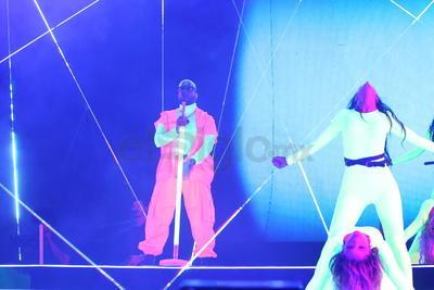 """El reguetonero apareció """"custodiado"""" por varias bailarinas que, al igual que él, portaban vestuario en tonos neón."""