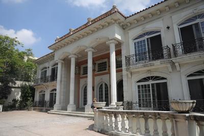 Cuatro columnas de unos cinco metros de altura con estilo neoclásico configuran el porche del que cuelgan doradas lámparas para iluminar la entrada a este edificio de tres pisos.
