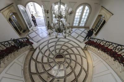Una doble escalinata en el vestíbulo, adornado con candelabros, dirige hacia el primer piso, donde hay un cuarto que hoy está vacío pero que antaño albergó 206 millones de dólares en efectivo, además de 17 millones de pesos (unos 892,000 dólares) y 200,000 euros pertenecientes a Zhenli Ye Gon.