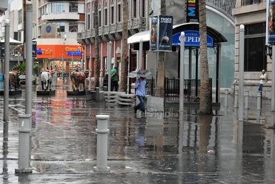 Peatones aceleran su paso ante la constante lluvia que se registró en el Centro de Torreón.