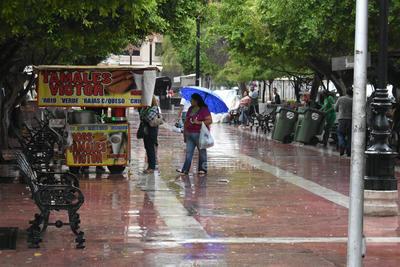 Ciudadanos se resguardan de la lluvia en la Plaza de Armas de Torreón.
