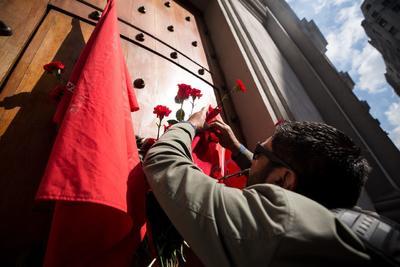 Un hombre coloca flores en la puerta de Morandé 80 del Palacio de La Moneda, por la que entraba el expresidente de Chile Salvador Allende.