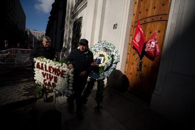 Un par de hombres portan este miércoles una corona floral durante uno de los actos en memoria del expresidente de Chile Salvador Allende, en conmemoración por el 46º aniversario del golpe de Estado de Augusto Pinochet, con el que se dio inicio a la dictadura militar del país austral entre 1973 y 1990.