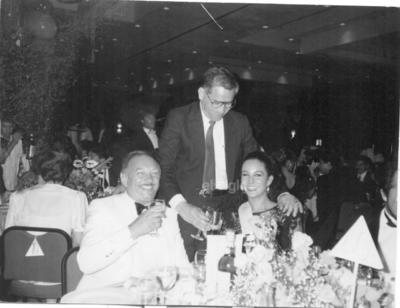 Año de 1989 en Cancún, Quintana Roo, durante la cena de gala del concurso Miss Universo. Valente Enríquez Mestas, brindando con Miss Italia, Silvana Conte, ganadora del 4o. lugar, los acompaña el multimillonario y famoso playboy musulmán Ali Khan.