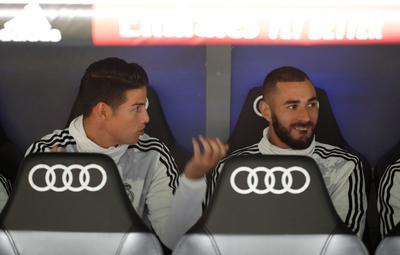 Los delanteros del Real Madrid, el colombiano James Rodríguez y el francés Karim Benzema, conversan en el banquillo al inicio del partido ante el Osasuna.