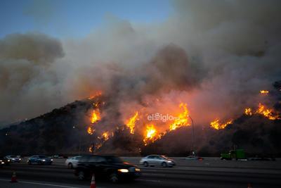 Vehículos transitan frente a un incendio cerca del Centro Getty en Los Angeles, Estados Unidos, el 28 de octubre de 2019. Miles de residentes fueron obligados a evacuar sus hogares después de que los incendios forestales de rápido crecimiento estallaran el lunes por la mañana cerca del famoso Centro Getty, en el oeste del estado estadounidense de California.