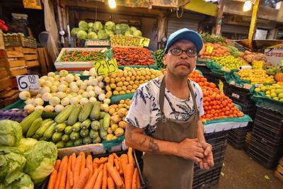 Personajes. Con 20 años, Juan Luis, es una de las otras personas que se instalan todos los días desde muy tempranas horas de la mañana para vender frutas y verduras sobre los pasillos del mercado a sus clientes.
