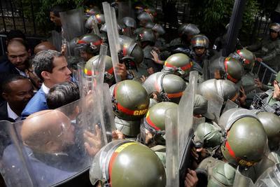 El líder opositor venezolano Juan Guaidó, acompañado de un grupo de opositores, forcejean con la policía al ver impedida su entrada a la sede de la Asamblea Nacional este domingo, en Caracas (Venezuela). Guaidó denunció que el país vivió este domingo