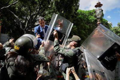 El líder opositor venezolano Juan Guaidó trepa una reja en un intento por ingresar a la sede de la Asamblea Nacional, custodiada por la policía para impedir su ingreso y el de diputados opositores este domingo, en Caracas (Venezuela). Guaidó denunció que el país vivió este domingo 'el asesinato de la República' al elegir el chavismo a un nuevo presidente de la Asamblea Nacional (AN, Parlamento) en una sesión a la que le impidieron entrar, así como a un grupo de diputados opositores. La trifulca comenzó cuando intentó acceder a la sede de la AN y fue repelido por los miembros de la GNB. Intentó entonces subir por una verja que da acceso al hemiciclo pero los agentes lo impidieron con los escudos