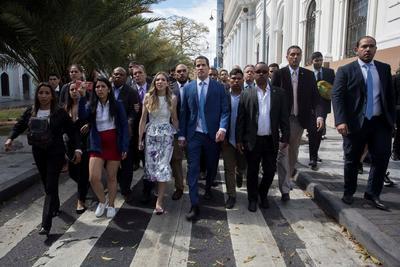 El líder opositor venezolano Juan Guaidó, acompañado de su esposa Fabiana Rosales y de un grupo de opositores, se dirigen hacia la entrada de la sede de la Asamblea Nacional este domingo, en Caracas (Venezuela). Diputados chavistas de la Asamblea Nacional (AN, Parlamento) eligieron como presidente del organismo a Luis Parra, antiguo miembro del partido Primero Justicia, en un bronco y breve debate al que no llegó Juan Guaidó, retenido durante horas por la Policía en los alrededores del Palacio Legislativo. Antes de la sesión, esperada desde hace meses como un nuevo pulso entre Gobierno y oposición, varios cordones de la de la Policía Nacional Bolivariana (PNB) y la Guardia Nacional Bolivariana (GNB, policía militarizada), impidieron los accesos al Parlamento con numerosos controles tanto a Guaidó como a otros diputados que lo acompañaban para el ingreso.