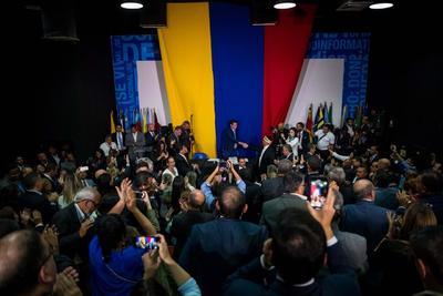 El presidente de la Asamblea Nacional, Juan Guaidó es juramentado en una sesión del Parlamento realizada en la sede de un periódico local, este domingo, en Caracas (Venezuela). El líder opositor fue reelegido como presidente del Parlamento de Venezuela durante una sesión paralela e improvisada de la Cámara, celebrada en la sede de un periódico, en la que solo participaron los diputados contrarios a Nicolás Maduro y de la cual no formó parte la bancada chavista.