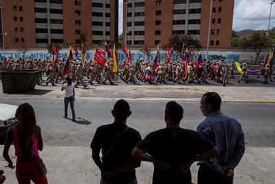Varias personas observan el lunes 12 de febrero una manifestación de milicianos, en Caracas.