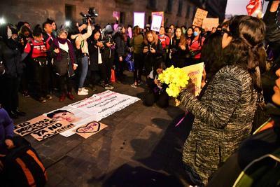 Encapuchadas y familiares de víctimas de feminicidio protestan afuera de Palacio Nacional, entre reclamos de justicia y pintas a una de las puertas del inmueble