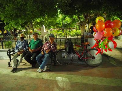 """Adultos mayores se concentran en la Plaza de Armas, aún cuando los eventos están suspendidos por la contingencia; muchos de ellos salen aunque sea """"un par de horas"""" a tomar el aire, pues dicen que no están acostumbrados a estar encerrados en casa."""