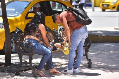 Arriesgan a menores. No son pocos los jóvenes que se arriesgan contagiarse por el COVID-19 al salir de casa sin cubrebocas y para actividades no esenciales. En la fotografía se observa a una pareja cambiando a su bebé en plena banca de la Plaza de Armas de Torreón.