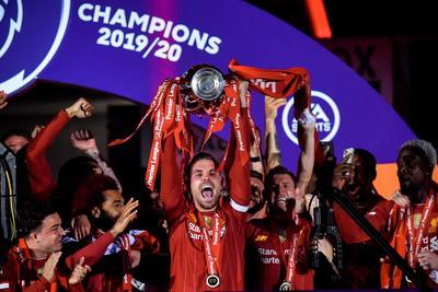 Liverpool (Reino Unido), 22/07 / 2020.- Jordan Henderson (C) de Liverpool levanta el trofeo de la Premier League después del partido de fútbol de la Premier League inglesa entre Liverpool FC y Chelsea FC en Liverpool.