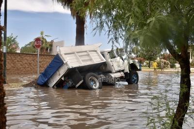 Hundimiento. Un camión materialista terminó hundido en plena vialidad en el fraccionamiento Senderos de Torreón tras las precipitaciones de ayer en la mañana.