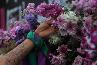 Llenan de flores vallas de Palacio Nacional por feminicidios