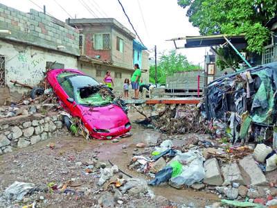 Caos y destrucción. Estos automóviles Camaro rojo y un Volvo, del mismo dueño, fueron arrastrados unos 500 metros por la fuerte corriente.