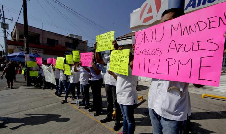 Empleados de farmacia incendiada marchan en Apatzingán