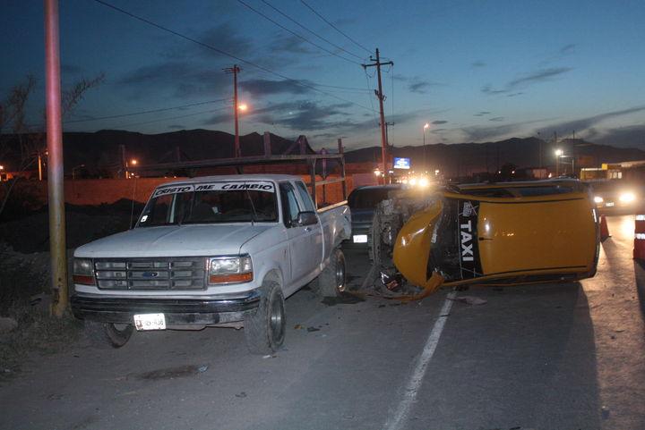 Vuelca conductor de taxi tras chocar con camioneta