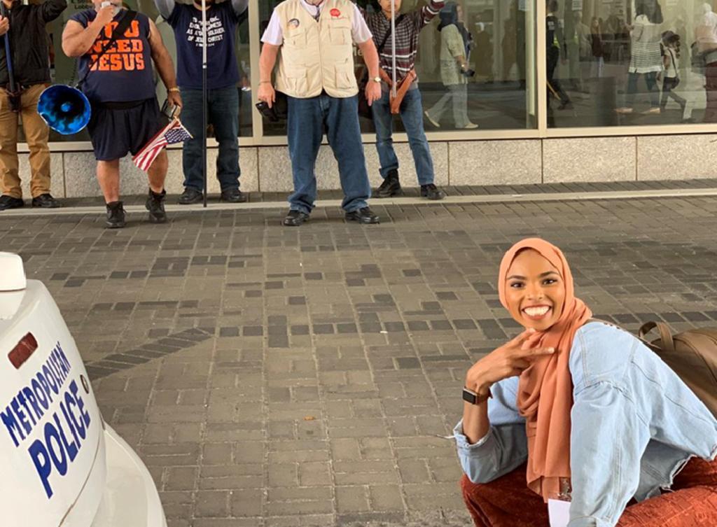 Shaymaa Ismaa'eel, musulmana, posa con una sonrisa frente a manifestantes en contra de aquella fe. (INTERNET)